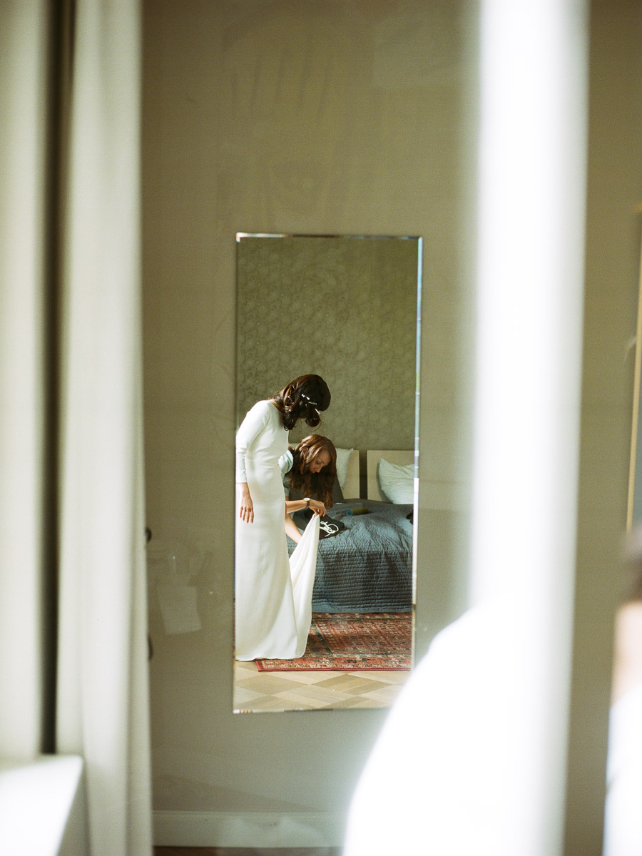 Braut beim Anziehen des Kleids